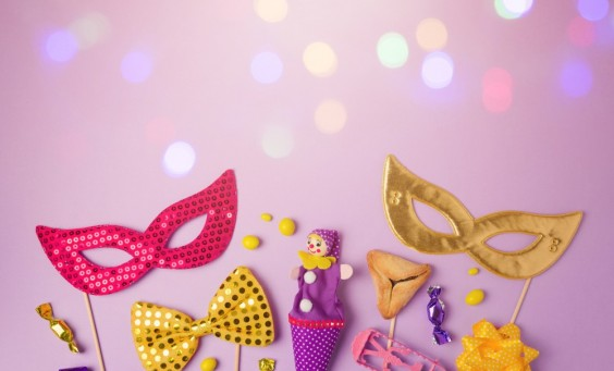 Purim holiday concept with carnival mask and party supplies on purple background with bokeh lights. Top view from above with copy space