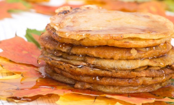pancakes topped with maple syrup lie on autumn maple leaves